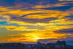 Dramatic yellowish sunset with cloudy sky over Cologne, Germany Stock Images