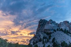 A dramatic Sky Behind Mount Rushmore. A dramatically colorful sky developing around sunset behind the four US presidents of Mount Rushmore, in North Dakota stock photo