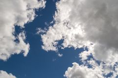 Dramatically illuminated billowy clouds brightly back lit, blue sky. Royalty Free Stock Image