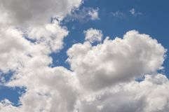 Dramatically illuminated fluffy clouds brightly back lit, blue sky. Stock Photography