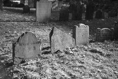 Dramatically lit ancient grave stones. In black and white in bright sun light on a beautiful winter's day Stock Image