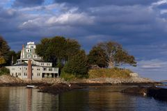 Dramatically lit house on the coast in historic marblehead massa. Dramatically lit house on the water's edge with trees, clouds, and beautiful reflections in the Royalty Free Stock Photography