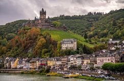 Dramatisch fairytale middeleeuws kasteel in Cochem Duitsland met Cochem-dorp langs de Rivier van Moezel stock afbeeldingen