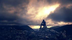 Dramatisch Silhouet van Mensenzitting op Berg Ridge Over Looking Stormy Skies stock foto's