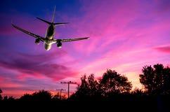 Dramatisch verlicht vliegtuig tijdens verbazende zonsondergang Royalty-vrije Stock Foto's