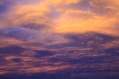 Dramatische en kleurrijke bewolkte zonsonderganghemel met viooltje en wenken Stock Foto's