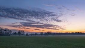 Dramatische gekleurde wolken boven een weide bij schemering, Nederland royalty-vrije stock fotografie