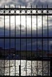 Dramatische hemel bij zonsondergang tegen de achtergrond van een rooster van ijzeromheining Royalty-vrije Stock Fotografie