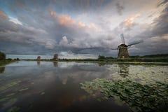 Dramatische hemel meer dan drie windmolens in Nederland stock afbeelding