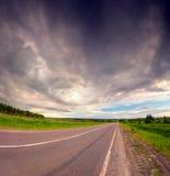 Dramatische hemel onder het asfaltweg van het land. Royalty-vrije Stock Foto's