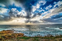 Dramatische hemel over de rotsachtige kust van Alghero stock afbeeldingen