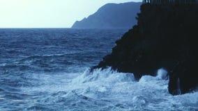 Dramatische krachtige oceaangolven die en in rotsachtige klip, langzaam-mo bespatten breken stock video