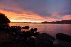 Dramatische zonsonderganghemel in de overzeese baai Stock Foto's