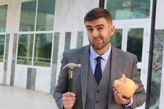 Dramatisk affärsman omkring som bryter hans spargris royaltyfria foton