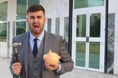 Dramatisk affärsman omkring som bryter hans spargris arkivfoto