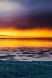 Dramatisk apelsin- och violetsolnedgång över en vintrig sjö Royaltyfria Bilder
