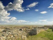 Dramatisk blå himmel med vita moln över fördärvar av gammalgrekiskakolonin av Histria, på kusterna av Black Sea Histria är Arkivfoto