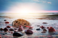 Dramatisk färgrik solnedgång på en stenig strand baltiska estonia nära havssomethere tallinn Fotografering för Bildbyråer