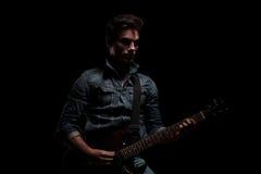 Dramatisk gitarrist som spelar på hans elektriska gitarr Royaltyfria Bilder