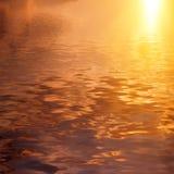 Dramatisk guld- himmel reflekterad i vatten royaltyfria bilder