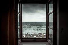 Dramatisk havssikt från öppnat fönster med stora stormiga vågor och dramatisk himmel under regn och stormväder i nedgångsäsong på Arkivbild