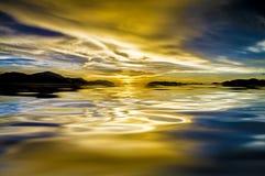 Dramatisk himmel- och solnedgångreflexion på vatten Arkivfoto