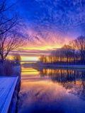 Dramatisk och f?rgrik soluppg?ng ?ver ett h?rligt flodlandskap arkivfoto
