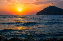 Dramatisk orange solnedgång över den turkiska stranden av Gumusluk Arkivfoto
