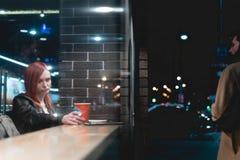 Dramatisk plats, flicka som arbetar på bärbara datorn i kafét, hållsmartphone i händer, penna, brukstelefon Freelanceren arbetar  royaltyfria bilder