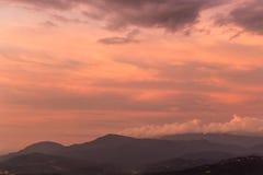 Dramatisk purpurfärgad himmel över dimmiga kullar Royaltyfria Foton