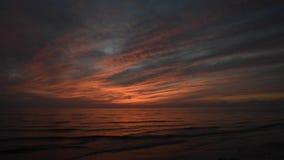 Dramatisk röd solnedgång med vågor som kommer till kusten stock video