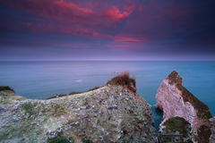 Dramatisk röd soluppgång över klippor i havet Fotografering för Bildbyråer