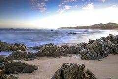 Dramatisk seascapesolnedgång med orange himlar och reflexioner Arkivbild