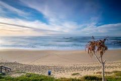 Dramatisk seascapesolnedgång med orange himlar och reflexioner Arkivfoton