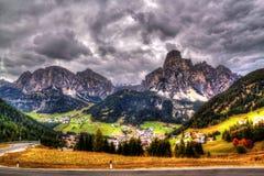 Dramatisk sikt av de italienska fjällängarna och staden av Corvara, italienska Dolomites royaltyfri fotografi