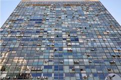 Dramatisk sikt av den gamla exponeringsglasbyggnadsfasaden med hänga för enheter för luft betingande arkivfoto