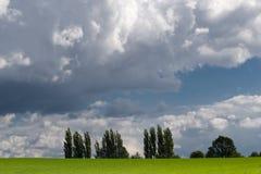 Dramatisk sky över grönt fält Arkivbilder