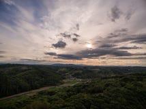 Dramatisk solnedgång över gröna kullar Royaltyfri Bild