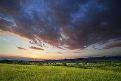 Dramatisk solnedgång över grönt fält Royaltyfri Fotografi
