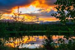 Dramatisk solnedgång i bergen Ljuset av den blekna dagen, som en brand i träna Arkivbilder