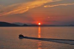 Dramatisk solnedgång med fishigfartyget Arkivfoto