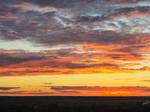 Dramatisk solnedgång med moln Arkivfoto
