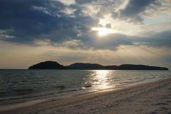 Dramatisk solnedgång med molnig himmel på stranden arkivbilder