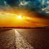 Dramatisk solnedgång och vit linje på asfaltvägen Royaltyfri Foto