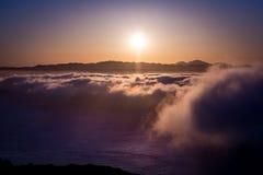 Dramatisk solnedgång ovanför molnen Arkivfoton
