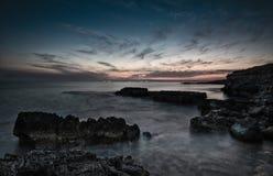 Dramatisk solnedgång på en stenig kustlinje royaltyfri foto