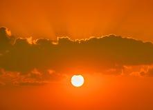 Dramatisk solnedgång med solen som skiner till och med moln Royaltyfri Fotografi