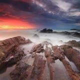 Dramatisk soluppgång över stenig shoreline arkivfoto