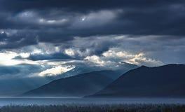 Dramatisk soluppgång i bergen med den tjocka vintergröna skogen i förgrund, Altai berg, Kasakhstan Arkivfoton