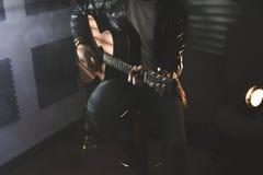 Dramatisk stående av en man som spelar en gitarr gitarrist royaltyfri bild